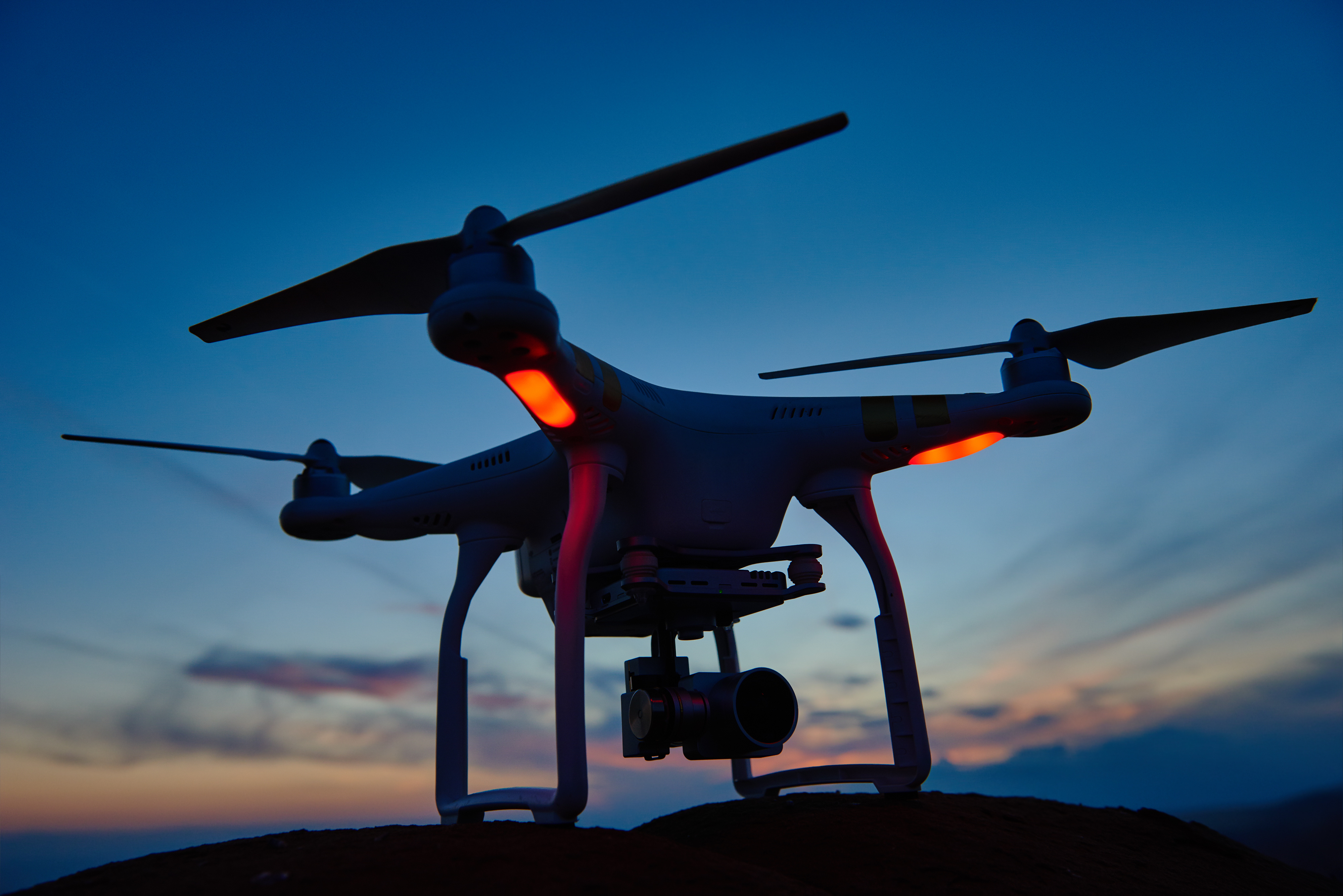 drone quadrocopter with high resolution digital camera ready to fly at sunset in